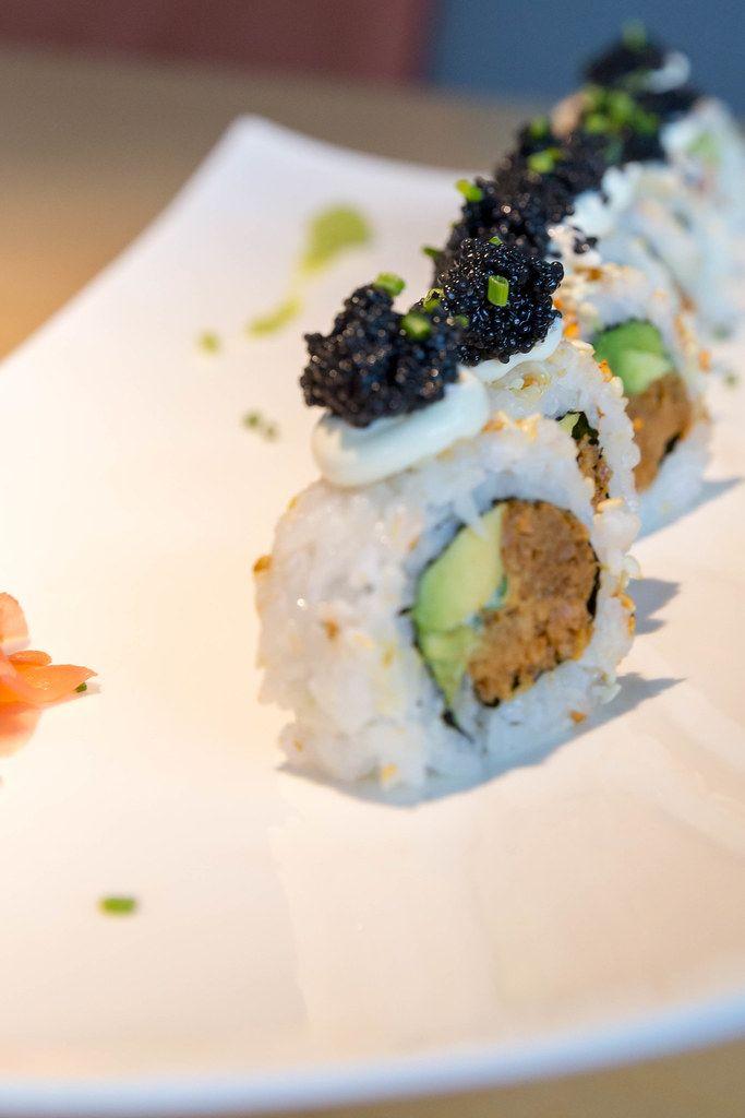 Veganes Sushi, aufgereiht auf einem weißen Teller, mit veganem Kaviar verziert, Avocadostückchen, Lauchzwiebel und veganem Thunfisch