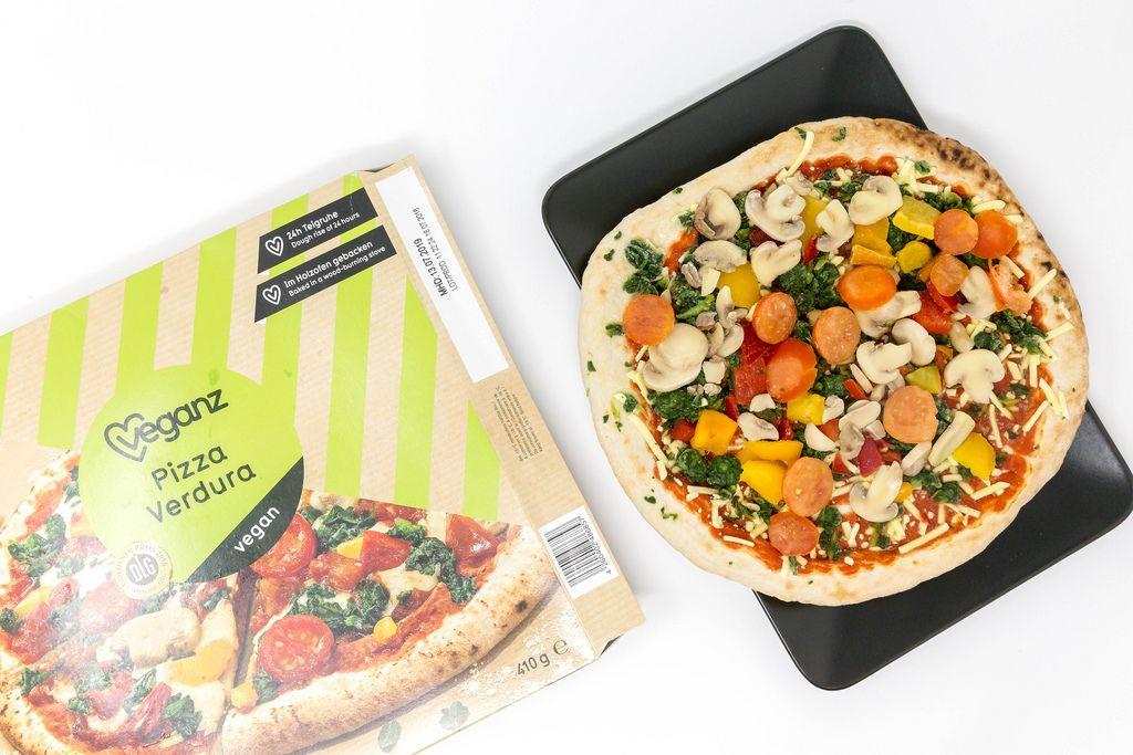 Veganz Pizza Verdura - Tiefkühlpizza mit Pilzen, Spinat, Paprika und Tomaten mit Verpackung in der Aufsicht auf einem schwarzen Teller und weißem Hintergrund