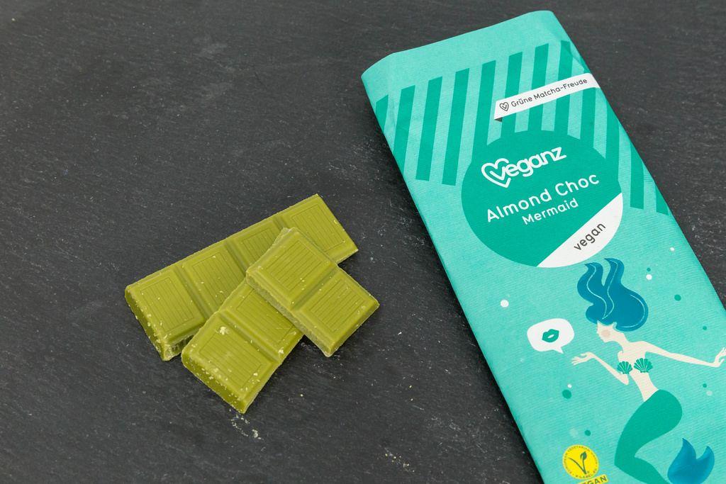 Veganz - vegane Bio-Mandelschokolade mit Matcha Grüntee-Extrakt mit Verpackung auf schwarzem Hintergrund