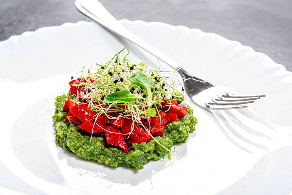 Vegetarian salad layers with fresh vegetables and onion seed sprouts on a white plate with fork