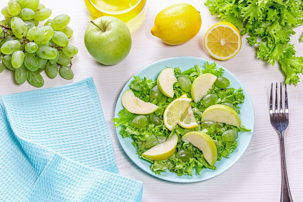 Vegetarian salad with lettuce, fresh Apple slices and grapes on the table with ingredients. Top view