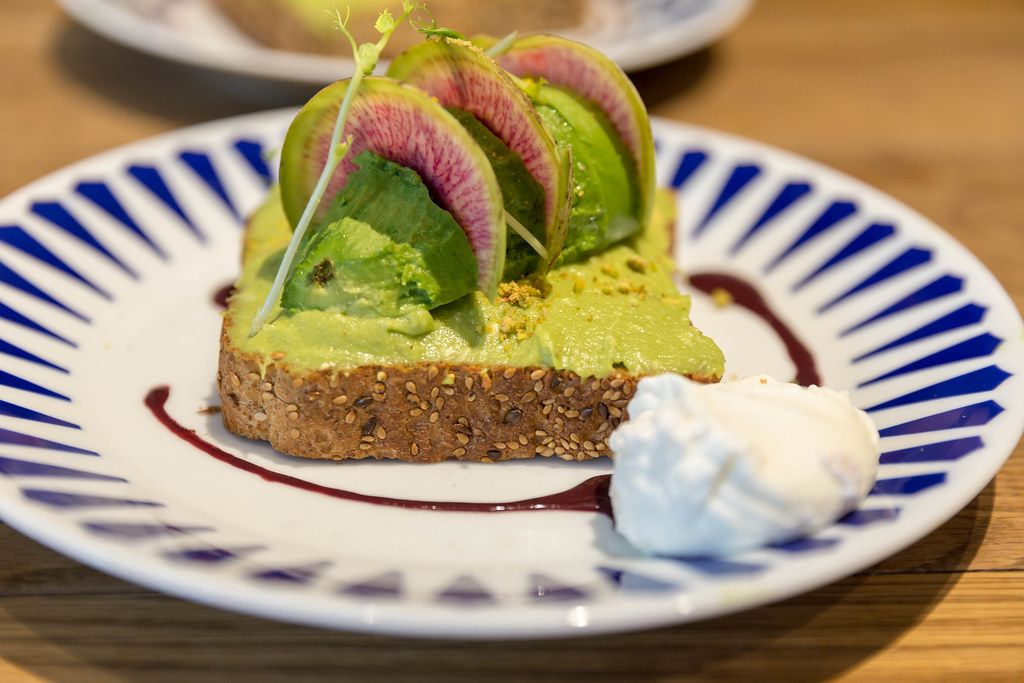 Vegetarian toast from whole wheat bread with guacamole, pistachio, yuzu & açai sauce, nutritional yeast and poached egg in close-up