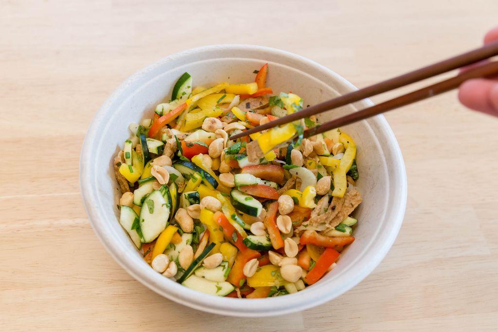 Vegetarische Gemüsepfanne mit Erdnüssen von Lieferservice wird mit Essstäbchen gegessen