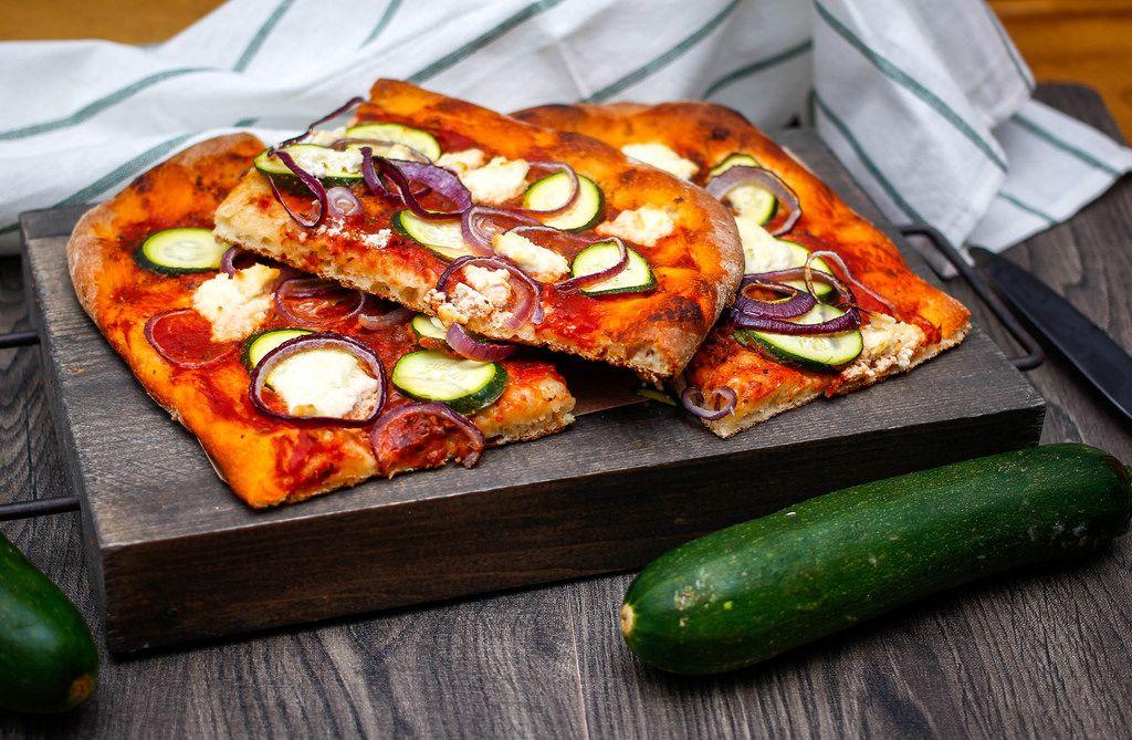 Vegetarische Pizza mit Zucchini und roten Zwiebeln auf einem Küchenbrett