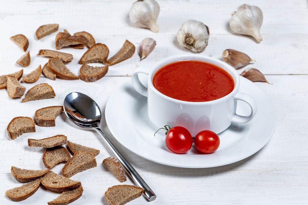 Vegetarische Tomatensuppe in weißer Tasse mit Kirschtomaten, Brotecken und Knoblauch auf einem weißem Holztisch