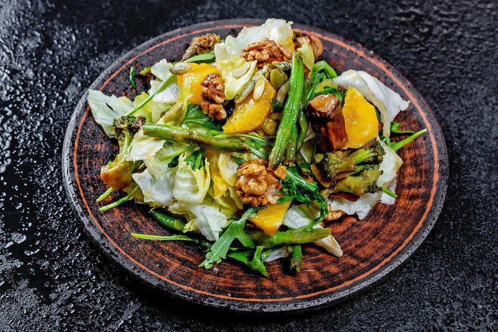 Vegetarischer Salat mit Spargel, Brokkoli, Pilzen, Rucola-Salat, Orangenstücke, Kerne und Nüsse, auf einem Holzteller auf einer schwarzen Abrbeitsfläche