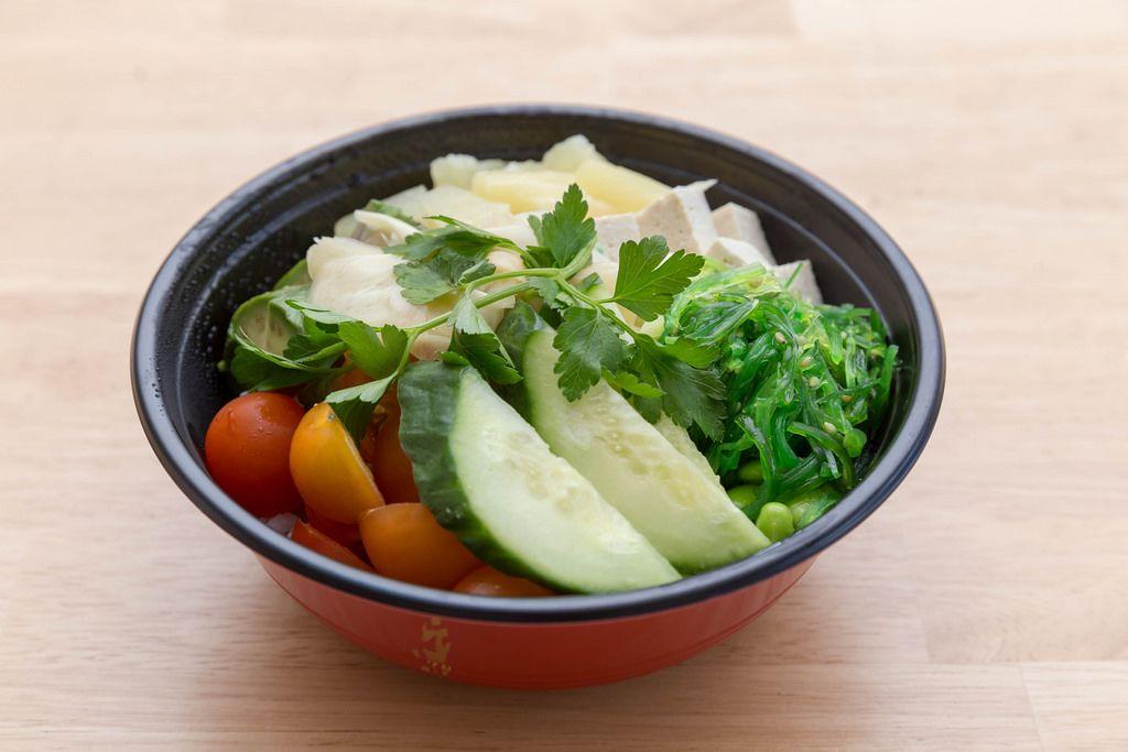 Veggie bowl salad with cucumbers, tomatoes, zucchini, pineapple, tofu and parsley