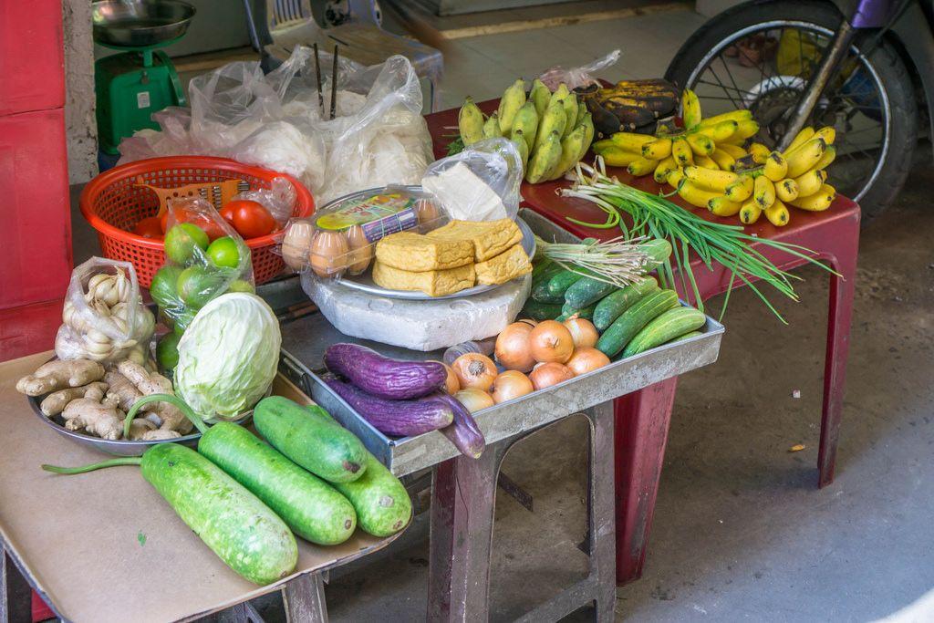 Verkaufsauslage eines kleinen Straßenhändlers mit Tofu, Eiern, Gemüse und Bananen in Saigon, Vietnam