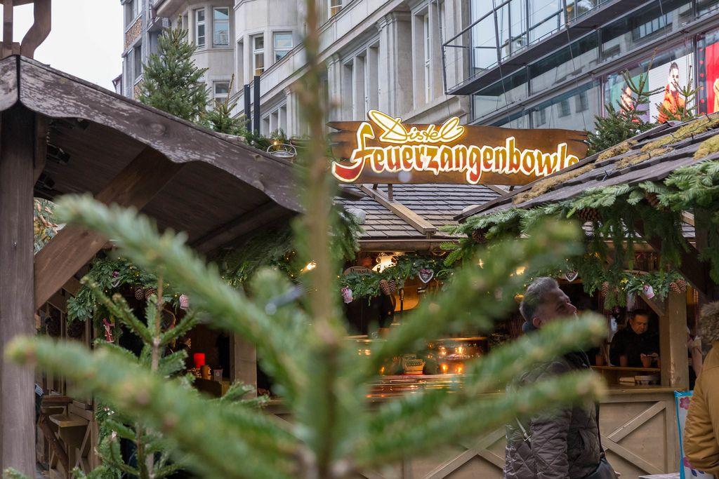 Verkaufsstand von Feuerzangenbowle an Weihnachtsmarkt, im Vordergrund Tannenbaum