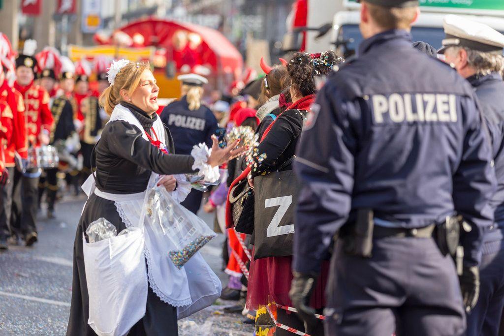 Verkleidete Frau bewirft Zuschauer mit Konfetti - Kölner Karneval 2018