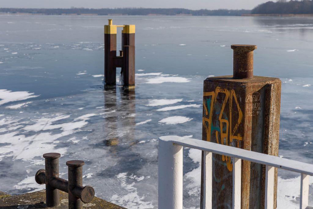 Verrosteter Stahlpfeiler und der zugefrorene Müggelsee im Hintergrund