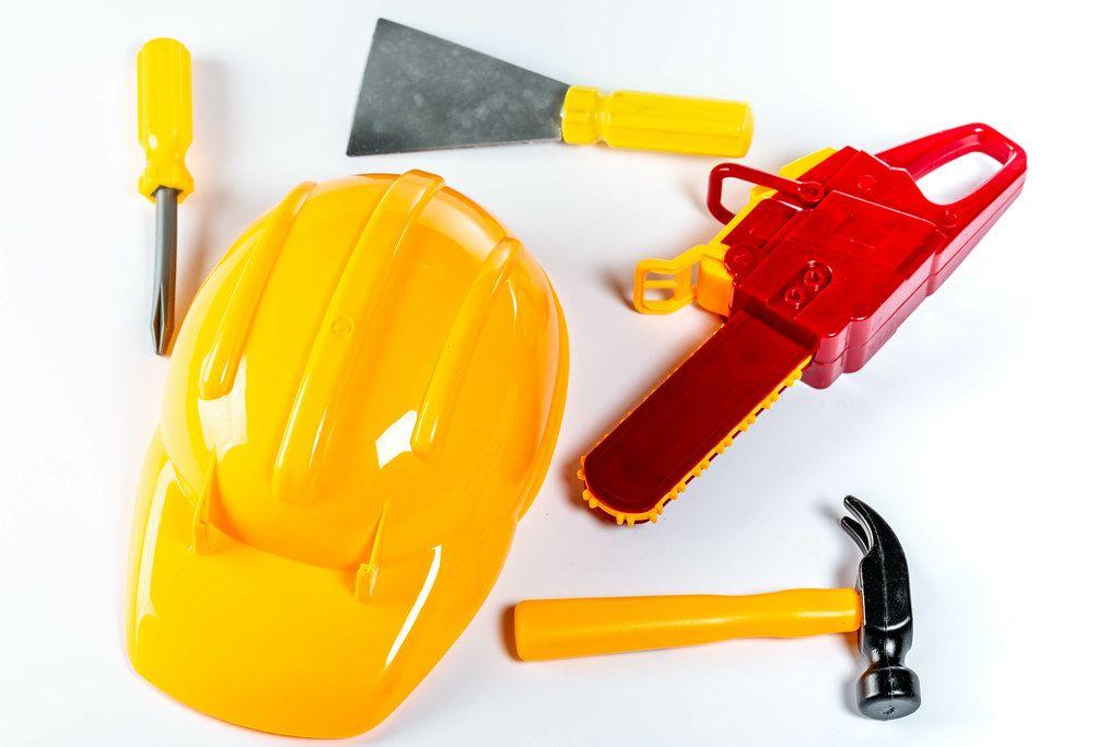 Verschiedene Bauarbeiter-Spielzeuge, wie ein gelber Helm, Hammer, Schraubenzieher, Spachten und eine Kettensäge