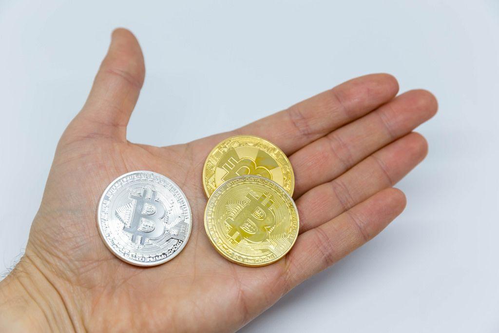 Verschiedene Bitcoin-Münzen in der Hand