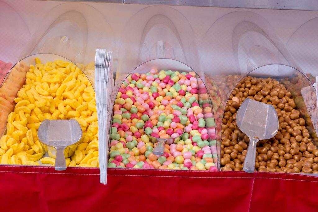Verschiedene bunte Süßigkeiten und Zuckerwaren in Kunststoffboxen mit Schaufel