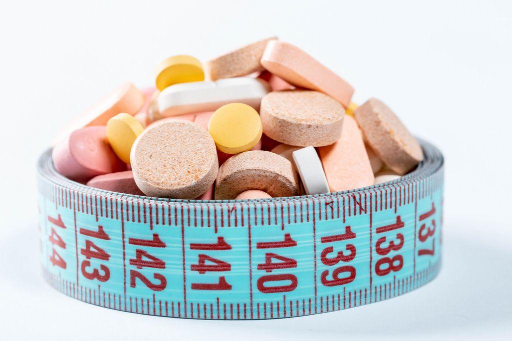 Verschiedene Diät-Pillen und Vitamintabletten zusammengehalten von Maßband vor weißem Hintergrund