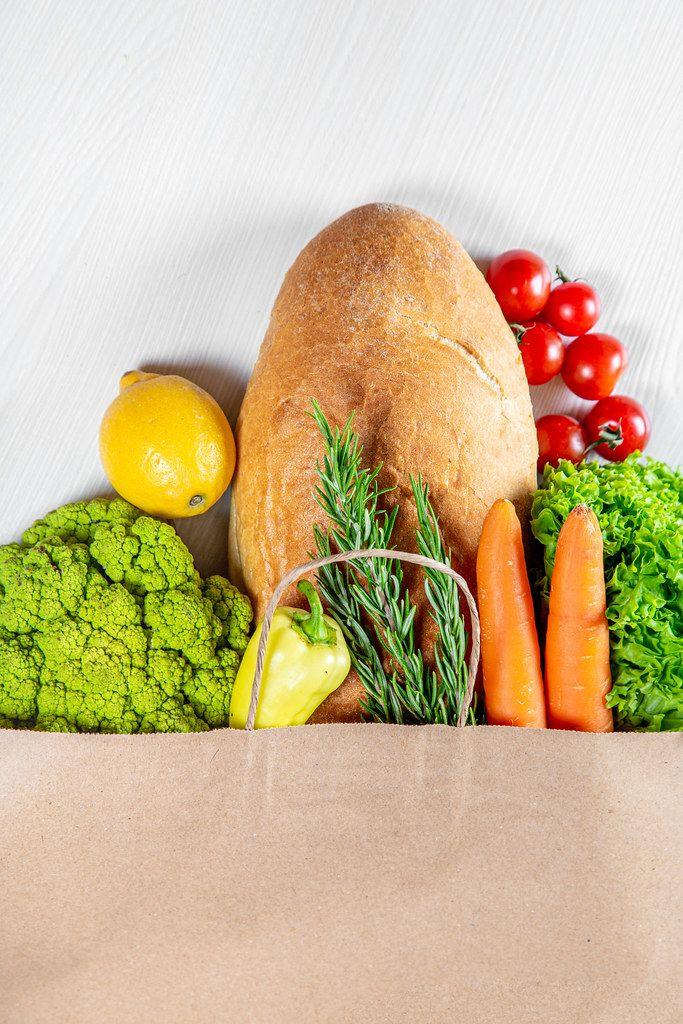 Verschiedene Gemüsesorten und Brot im Papierbeutel, auf einer weißen Holzoberfläche