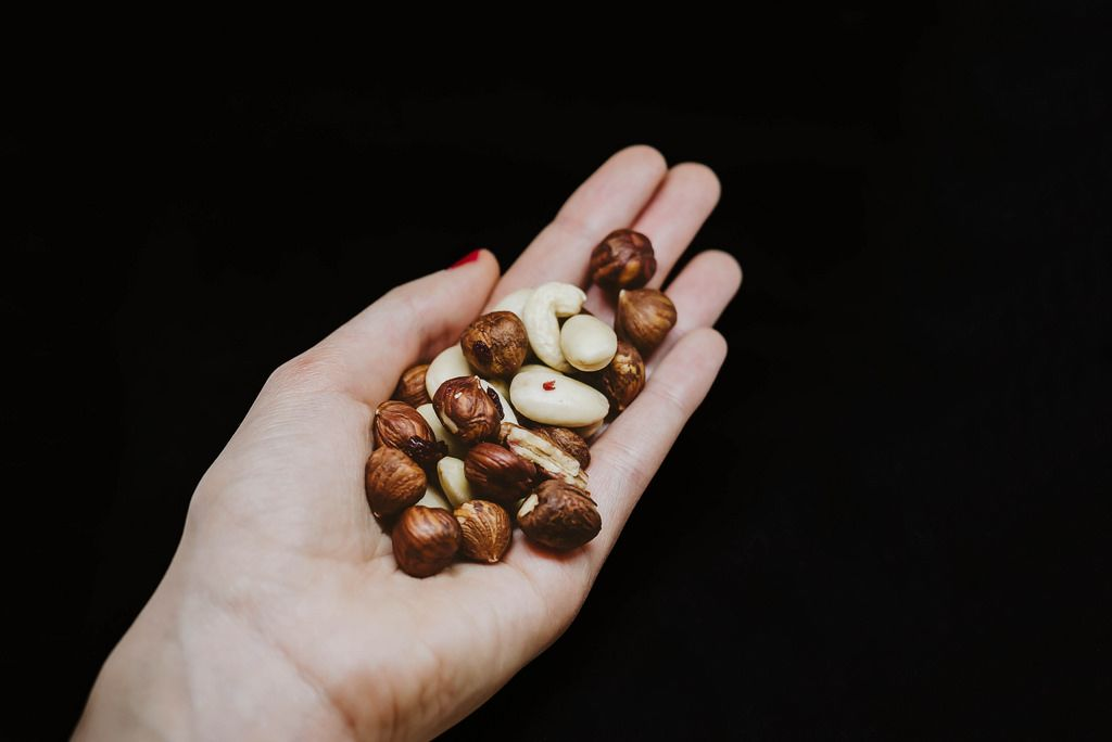 Verschiedene Nüsse in einer Hand im Studio, vor schwarzem Hintergrund