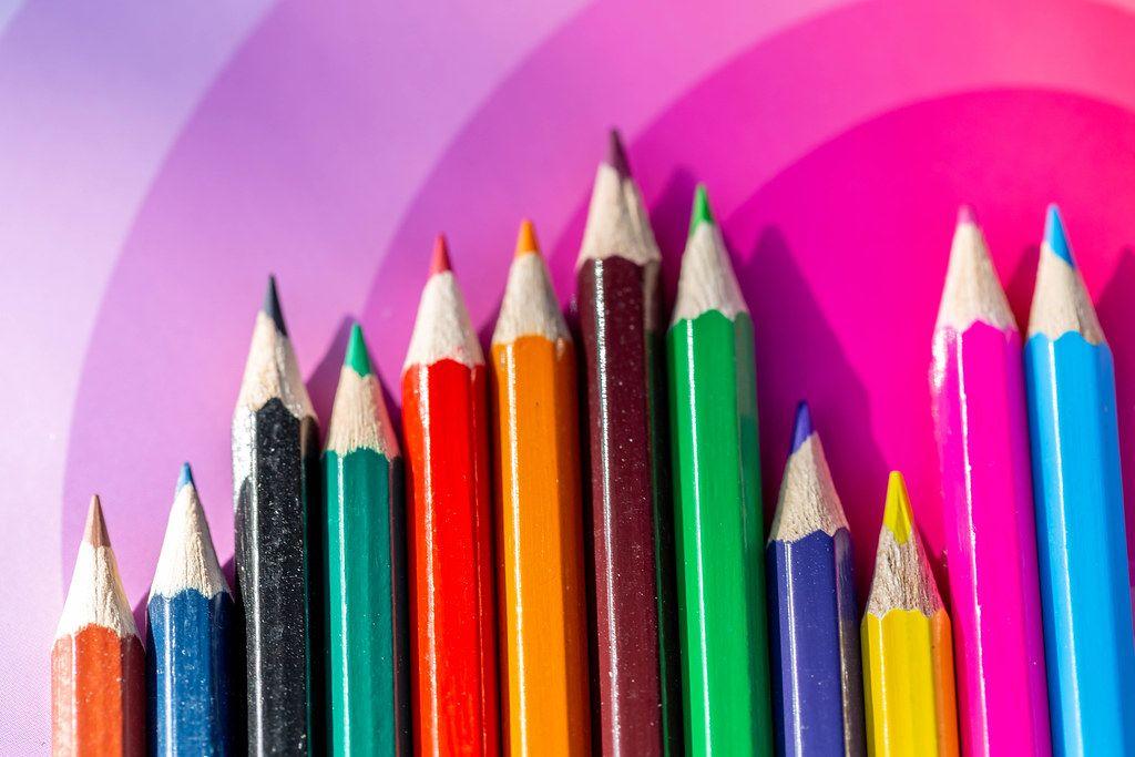 Verschiedenfarbige Buntstifte, aufgereiht auf einem rosa Untergrund