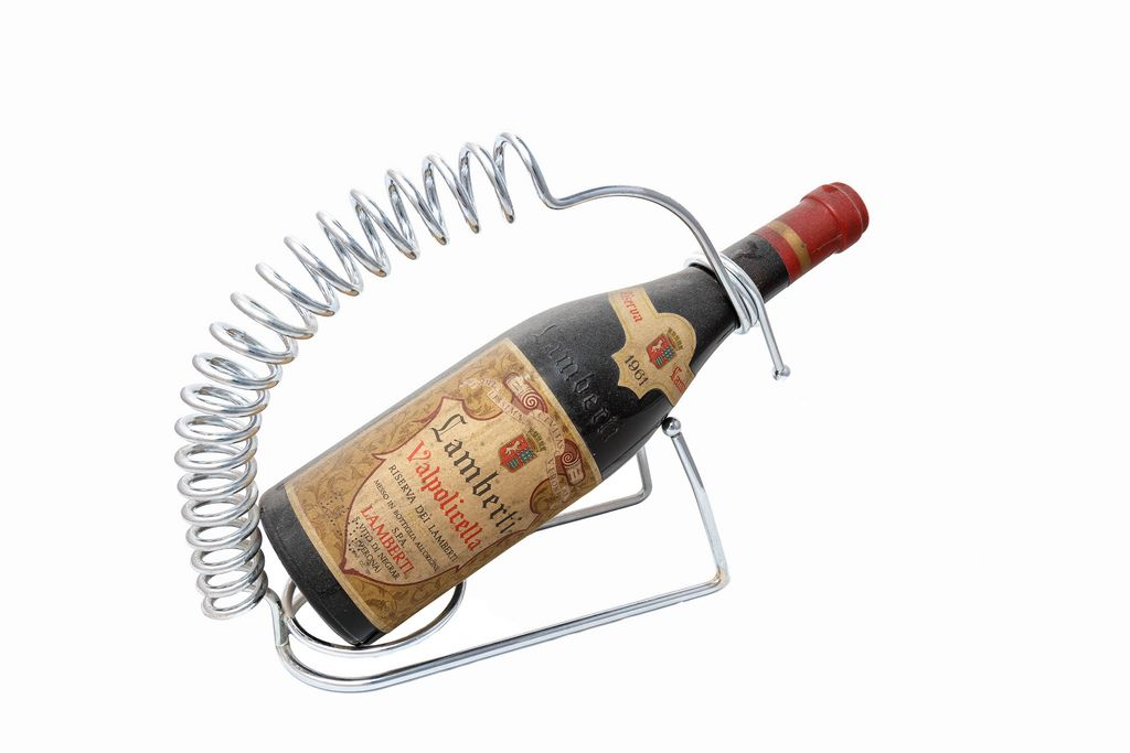 Very old bottle of red wine on white background