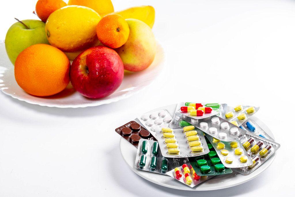 Viele bunte Tabletten und Medikamentenverpackungen vor einem Teller mit frischem, gesunden Obst