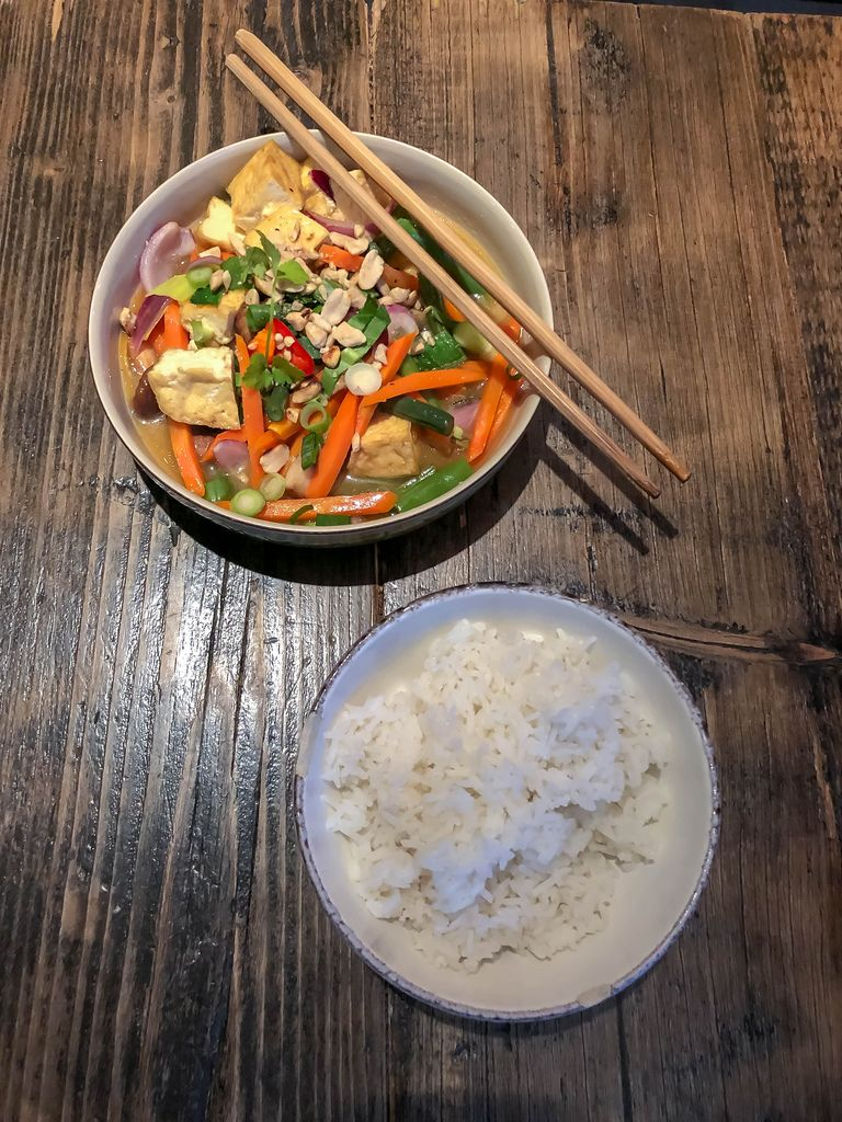 Vietnamesisches Gemüse-Gericht mit Reis auf Holztisch mit Essstäbchen