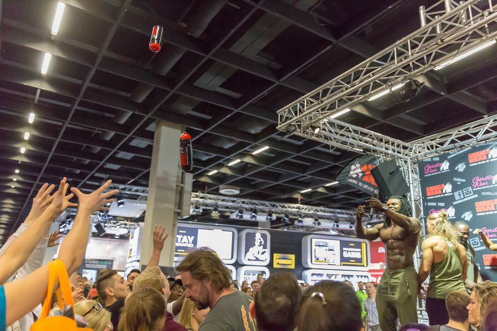 Visitors catching free sport plastic bottles thrown by Kevin Osazee - FIBO Cologne 2018