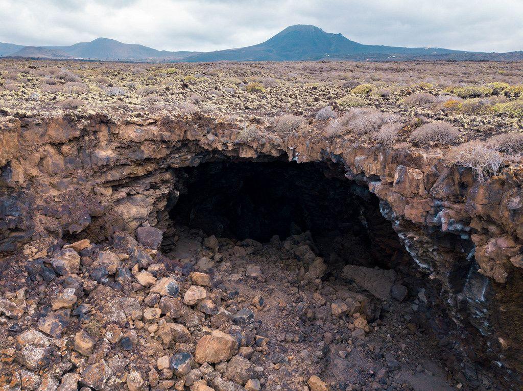 Volcanic cave in front of mountain range / Vulkanhˆhle vor Gebirgszug