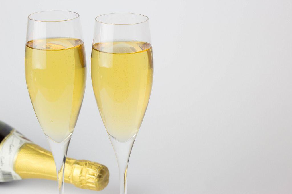 Volle Champagnergläser und Flasche vor weißem Hintergrund