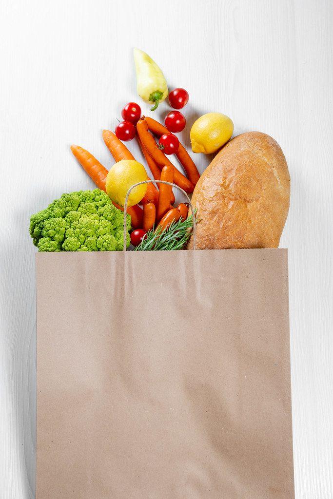 Volle Papier-Einkaufstüte mit gesunden Lebensmitteln für eine vegane Ernährung