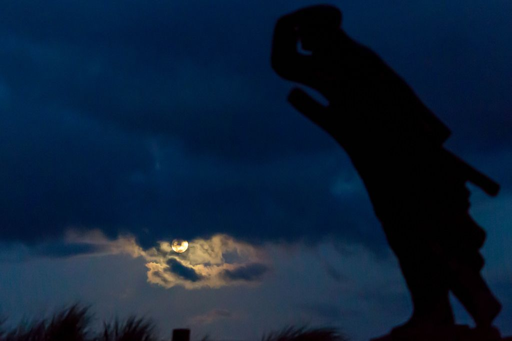 Vollmond bei bewölktem Himmel mit einer Statue im Vordergrund