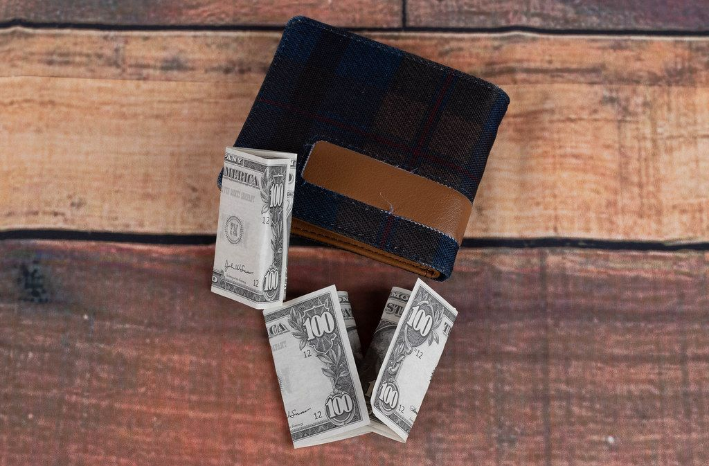 Wallet with dollar banknotes on wooden table