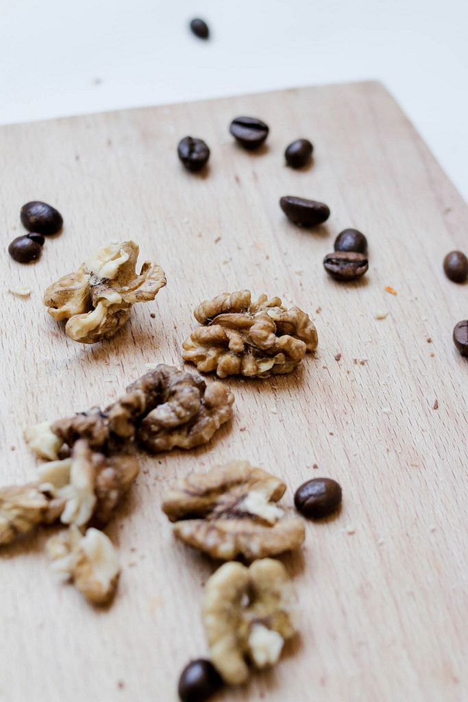 Walnuts and coffee beans on wood board