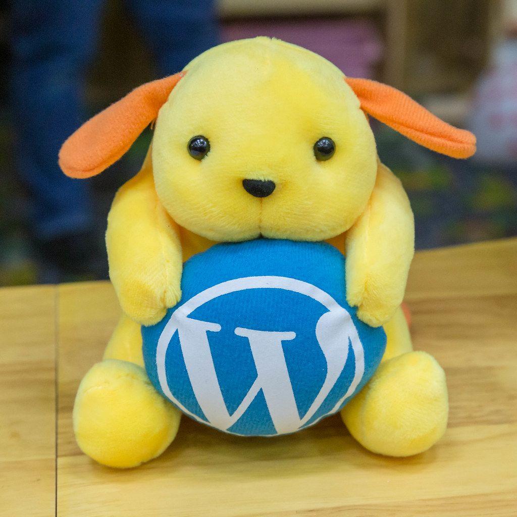 Wapuu plush toy with blue Wordpress logo at the BarCamp Bonn