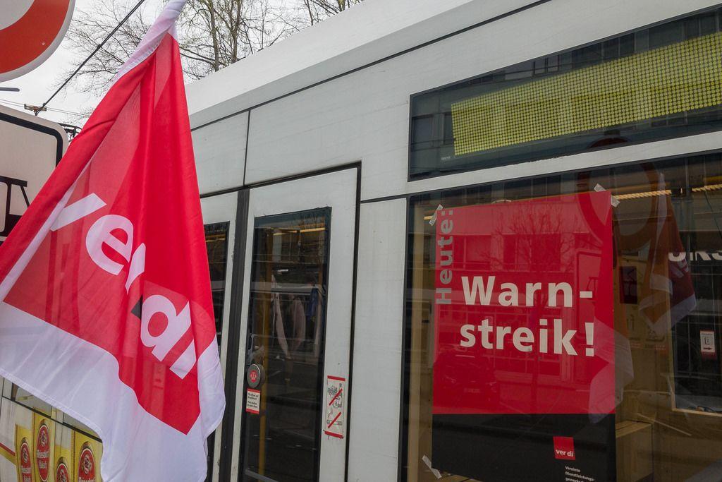 Warnstreik-Poster an einer Straßenbahn und eine Verdi-Fahne