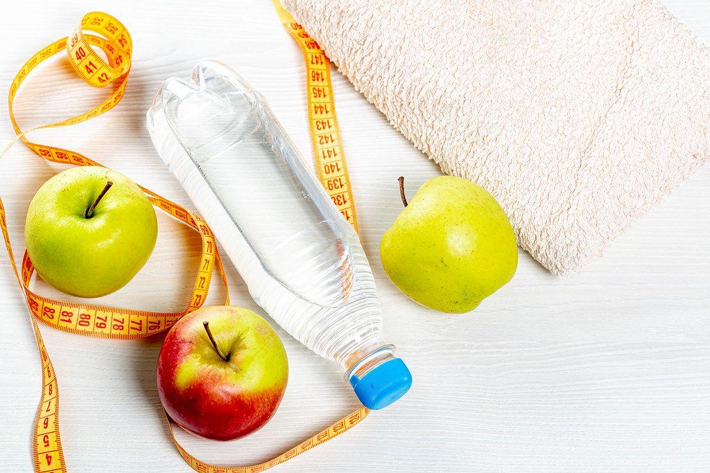 Wasserflasche, Äpfel, Bandmaß und ein Handtuch auf hellem Holztisch, aus der Vogelperspektive