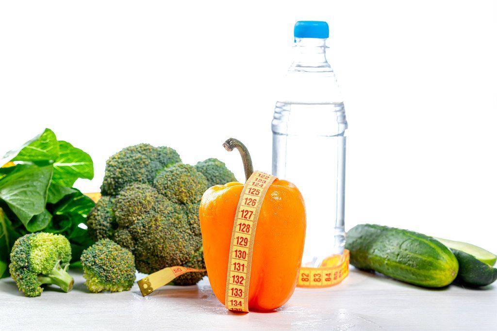 Wasserflasche und frisches Gemüse vor weißem Hintergrund mit Maßband - Konzept der Ernährung und Gesundheit - Lifestyle