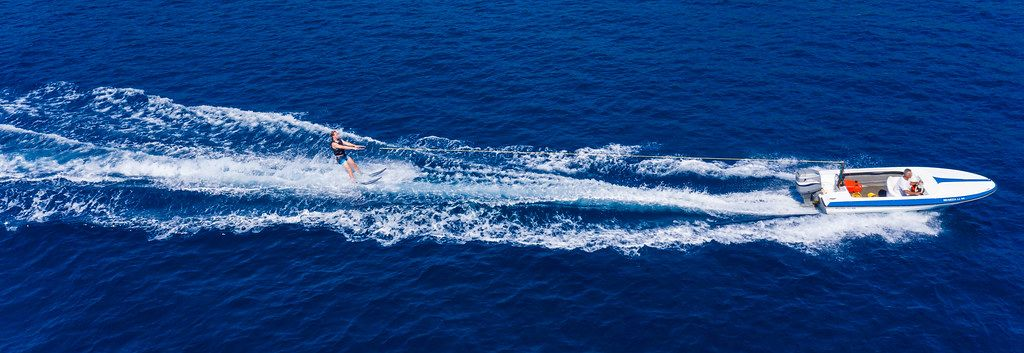 Wassersportler auf Wasserskis, wird von einem Motorsportboot über das blaue Meer gezogen und schlägt weiße Wellen, als Drohnenbild
