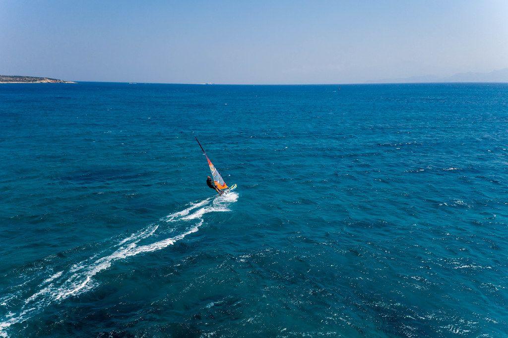 Wassersportler windsurft über die Wellen den blauen Mittelmeeres vor der griechischen Insel Paros