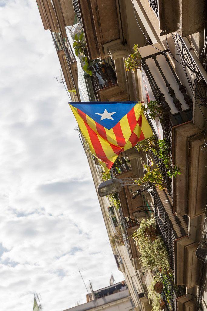 Wehende Estelada Flagge an einem gotischen Balkon in Barcelona, Spanien,  ist ein Symbol für die Unabhängigkeit Kataloniens