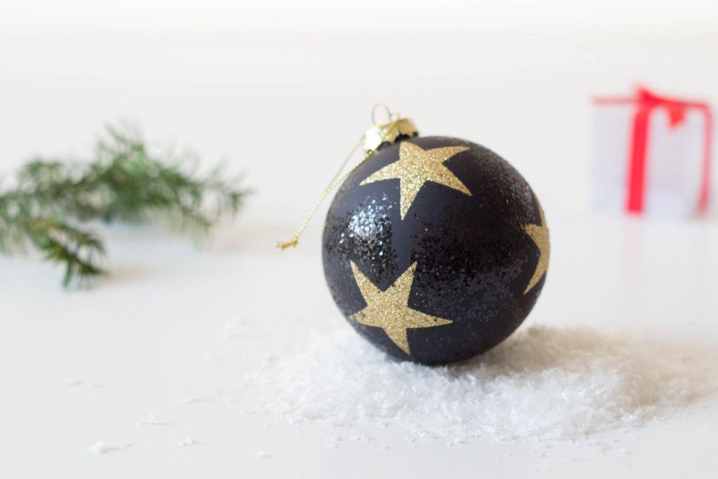Weihnachtsbaumkugel mit goldenen Sternen auf dem Schnee
