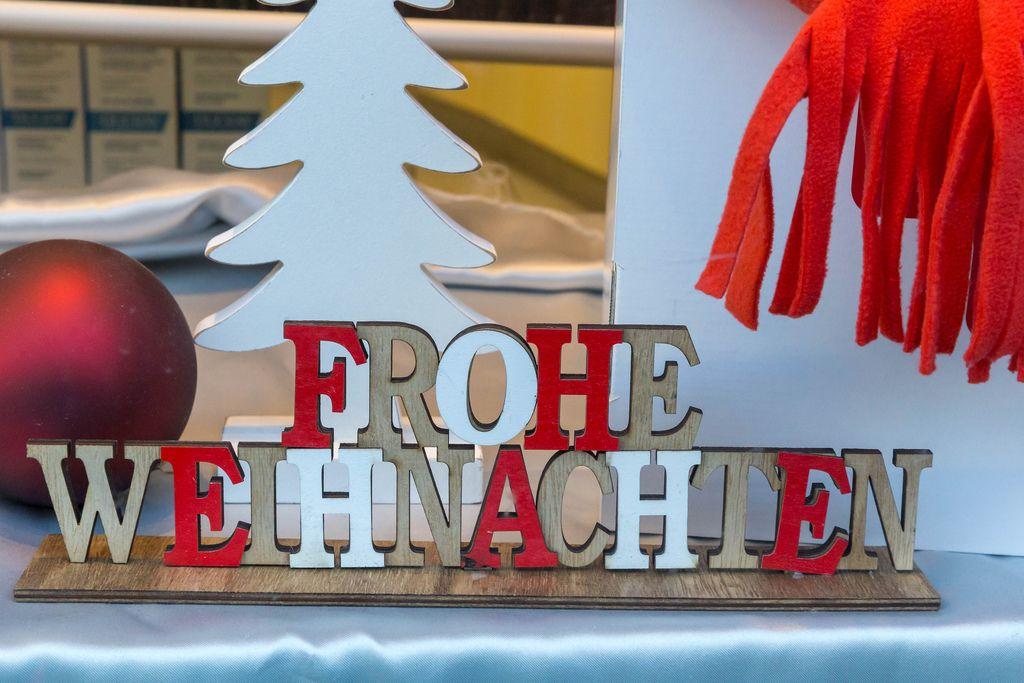 Weihnachtsdekoration Schriftzug frohe Weihnachten, weißer Tannenbaum und rote Weihnachtskugel