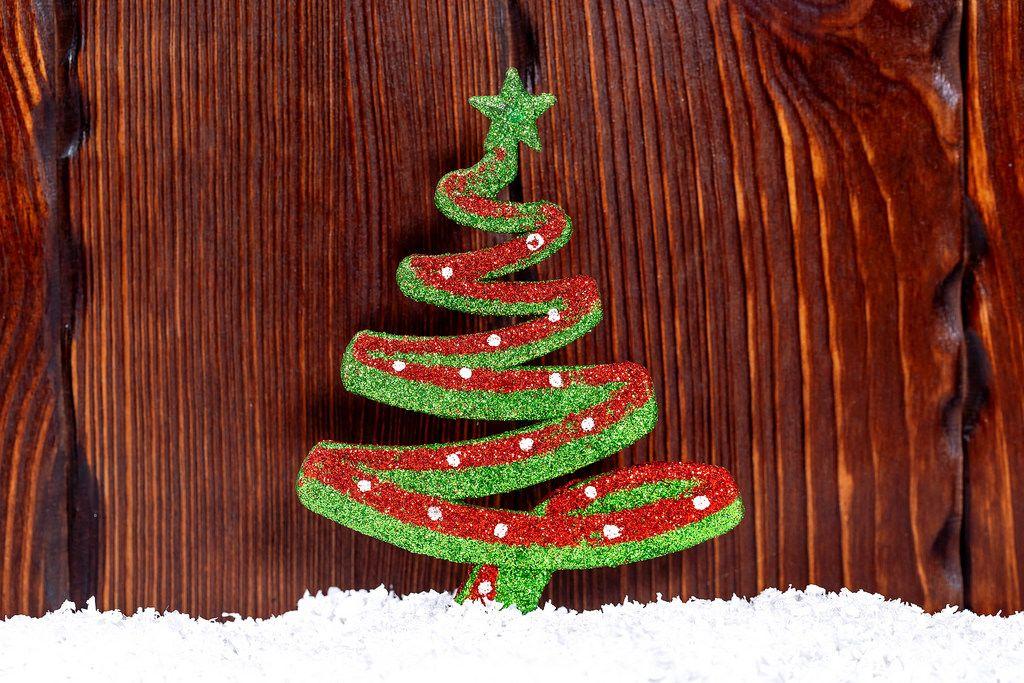 Weihnachtsdekoration, Weinachtsbaum mit Schnee auf hölzernem Hintergrund