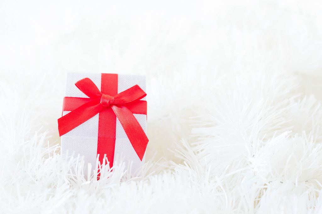 Weihnachtsgeschenk auf weißem Weihnachtsbaumschmuck