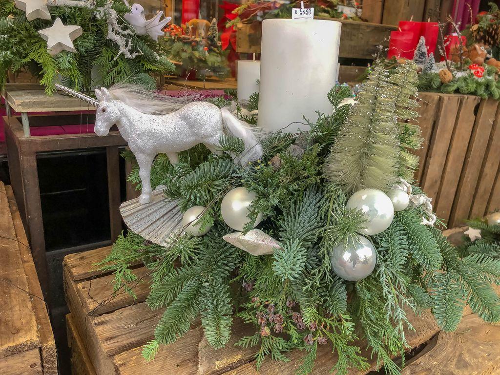 Weihnachtsgesteck mit Tannenzweigen, weißen Kerzen, perlmuttfarbenen Weihnachtskugeln und silbernem Einhorn in Verkaufsauslage, im Hintergrund weitere Weihnachtsdekoration und Adventskränze mit Sternen und Kerzen in rot