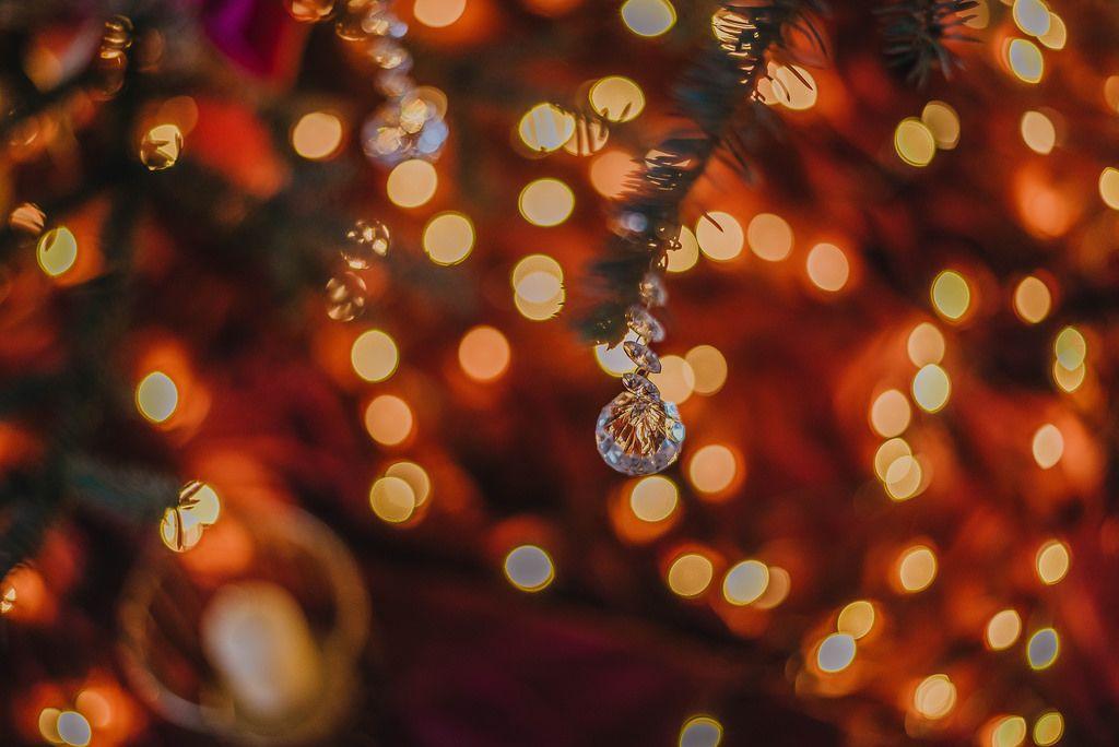 Weihnachtskristall an einem Tannenzweig mit Lichtern im Hintergrund