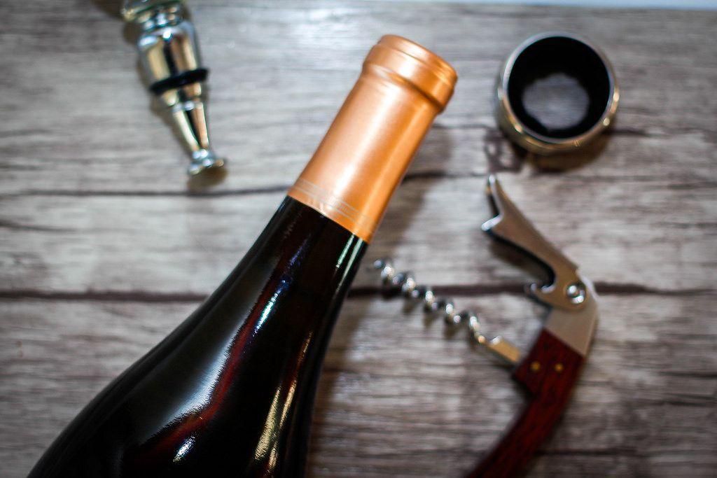 Weinflasche mit Korkenzieher und weiteren Utensilien