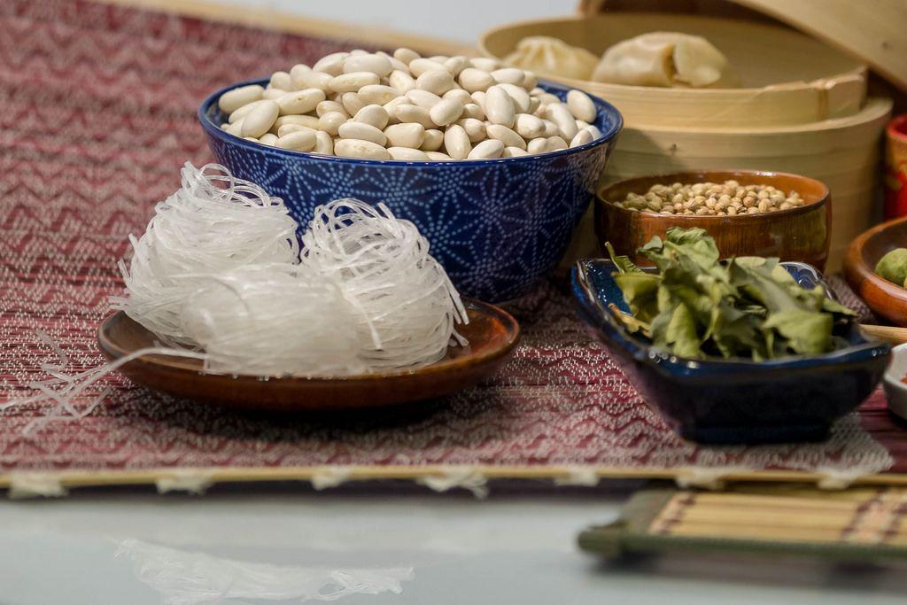 Weisse Bohnen, Glasnudeln und getrocknete Kräuter in Porzellanschalen