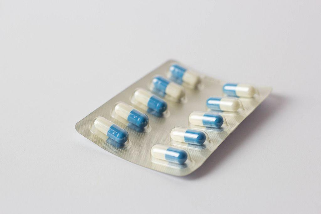 Weiß-blaue überzogene Tabletten vor weißem Hintergrund