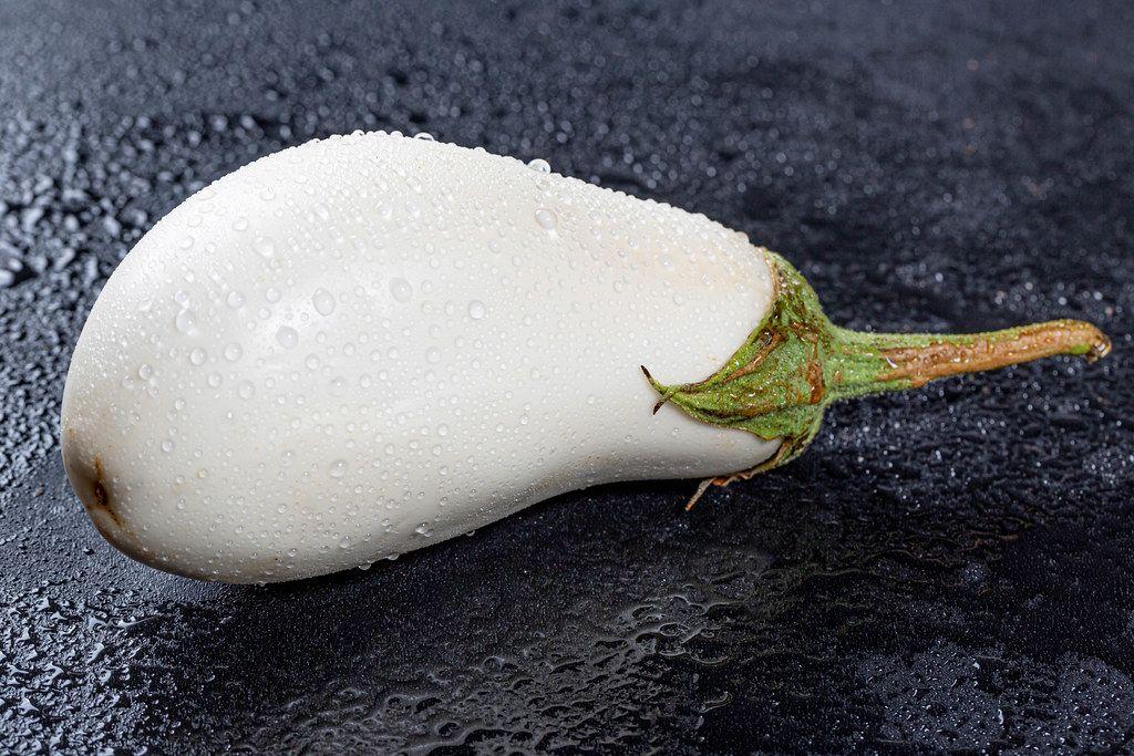 Weiße Aubergine mit Wassertropfen auf dunkler Oberfläche