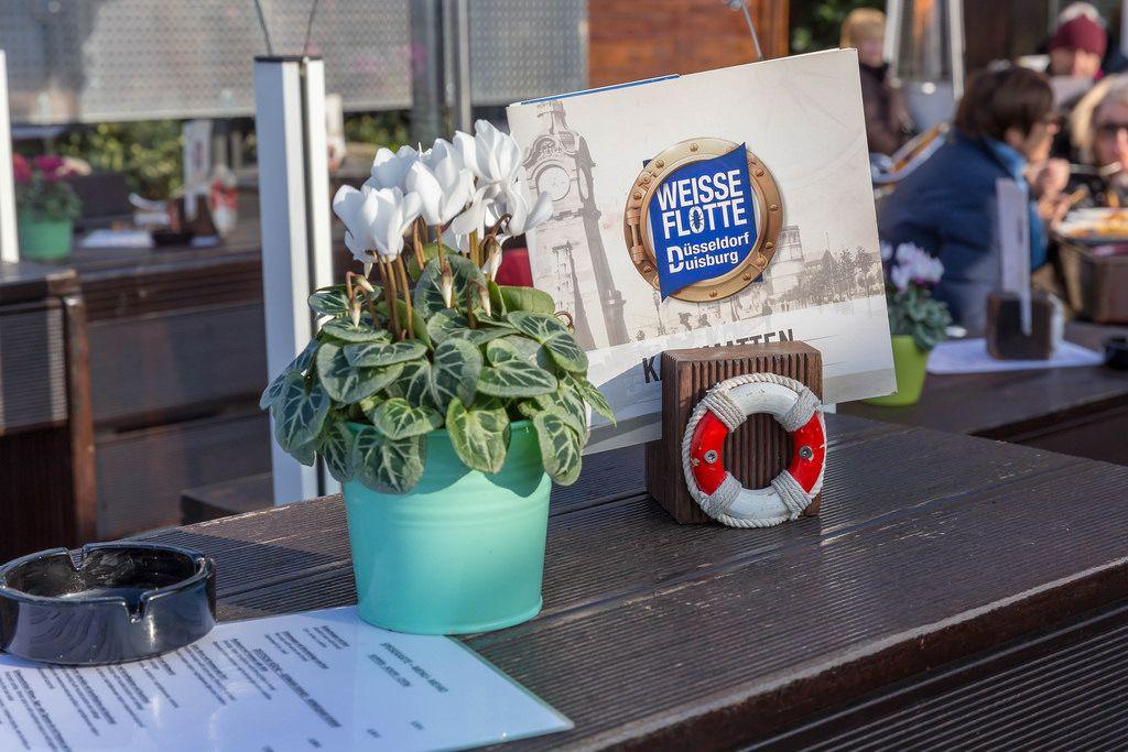Weiße Blumen und eine Getränkekarte auf dem Tisch in einem Lokal